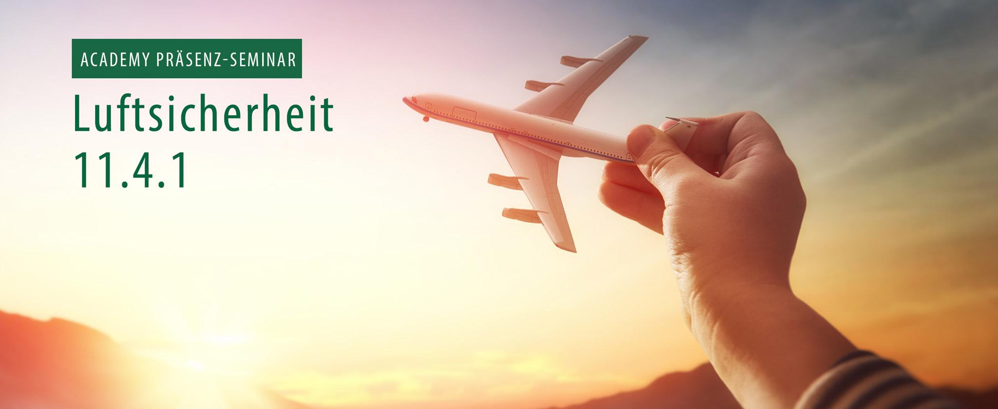 """Kinderhand hält Spielzeug-Flugzeug. Text """"Präsenzseminar Luftsicherheit 11.4.1"""""""